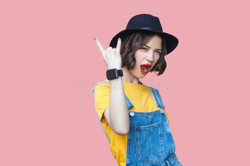 Portrait of beautiful amazed young woman in yellow t-shirt, blue denim overalls with makeup and black hat standing with rock horns. Screaming and looking at stock images