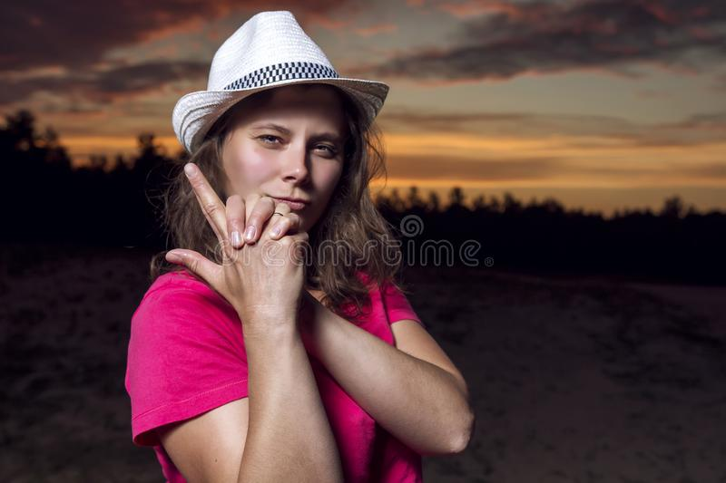Portrait of beautiful American girl in cowboy hat folded her arms with gun against beautiful sky at sunset royalty free stock images