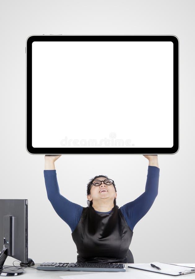 Beautiful businesswoman lifting a huge monitor stock image