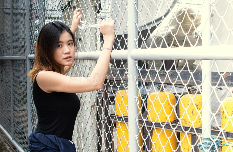 Portrait of a beautiful asian mechanist holding a wrench royalty free stock photos
