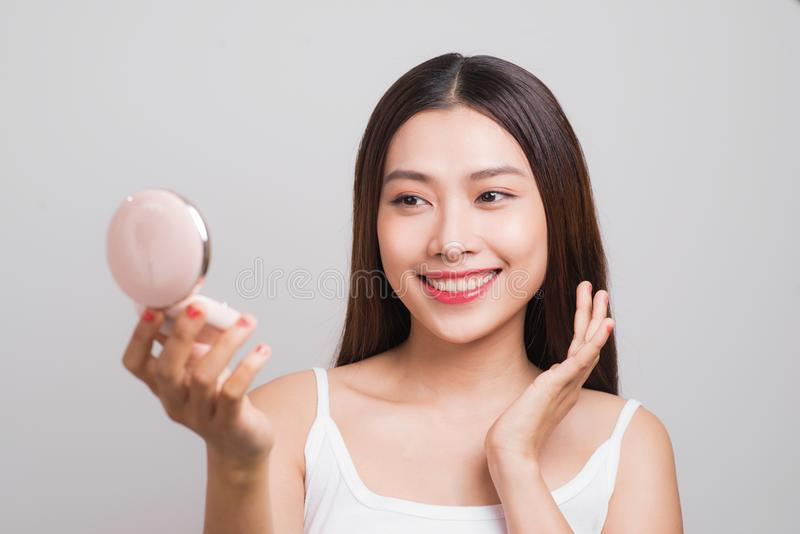 Portrait of beautiful asian woman checking powder makeup of cosmetic, beauty of girl with face smile isolated on white background stock image
