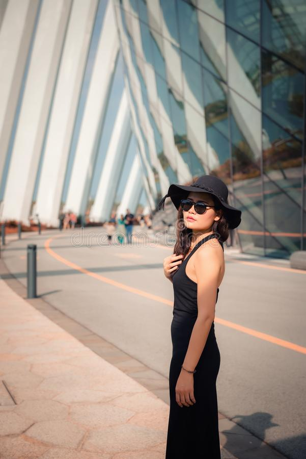 Portrait of Beautiful Asian Woman in Fashion Black Dress With Her Hat on Facade Building Background,  Beauty and Fashion Concept royalty free stock photography