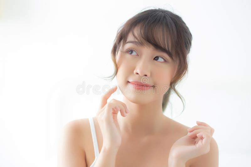 Portrait beautiful asian woman makeup of cosmetic, girl hand touch cheek and smile attractive. Face beauty perfect with wellness in the bedroom at home with stock photo