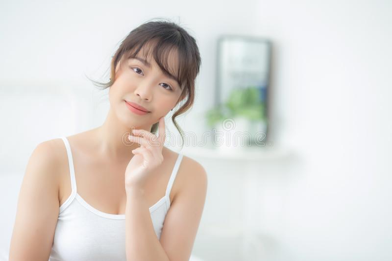 Portrait beautiful asian woman makeup of cosmetic, girl hand touch cheek and smile attractive. Face beauty perfect with wellness in the bedroom at home with royalty free stock photo