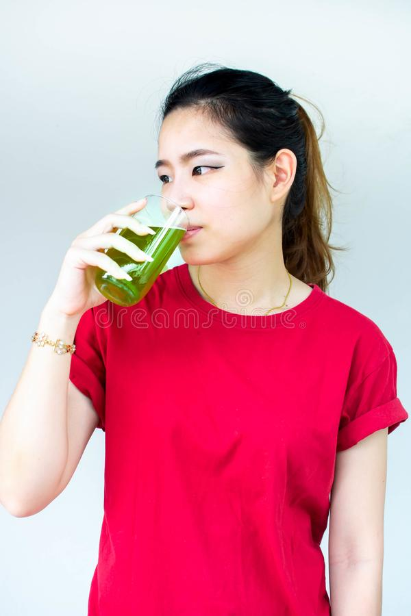 Woman in red shirt drinking green tea with white background stock image