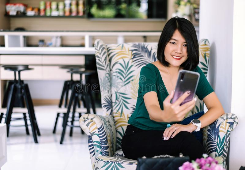 Portrait of beautiful Asian woman short hair selfie mobile while sitting on sofa in the restaurant,Happy and smiling,Positive thin stock image