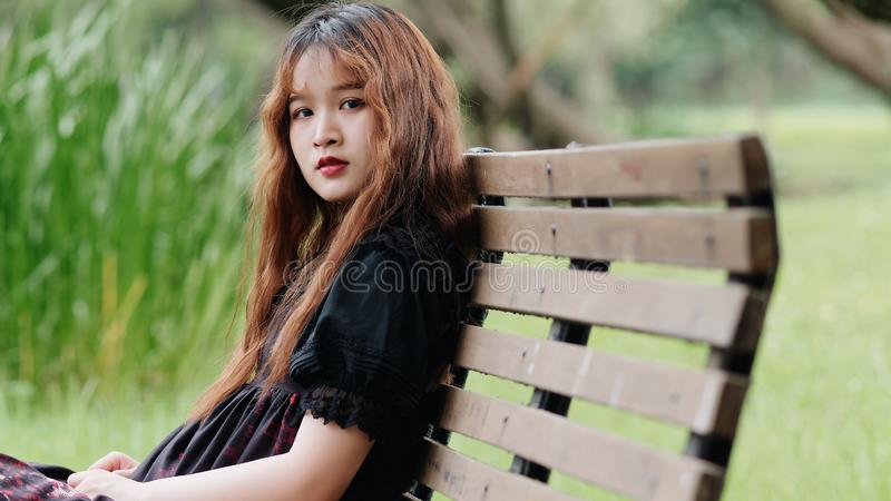 Portrait of beautiful Asian woman sitting on bench in summer forest, Chinese girl in vintage black dress looking at camera royalty free stock images