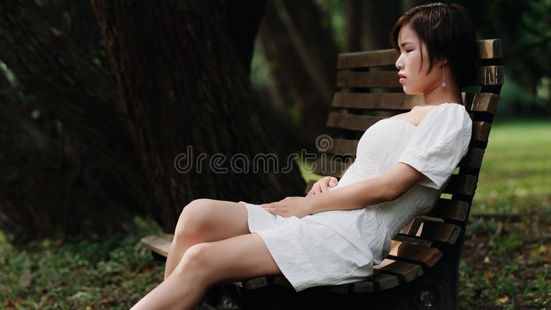 Portrait of beautiful Asian woman sitting on bench in summer forest, Chinese girl in white dress sleeping with eyes closed royalty free stock photography