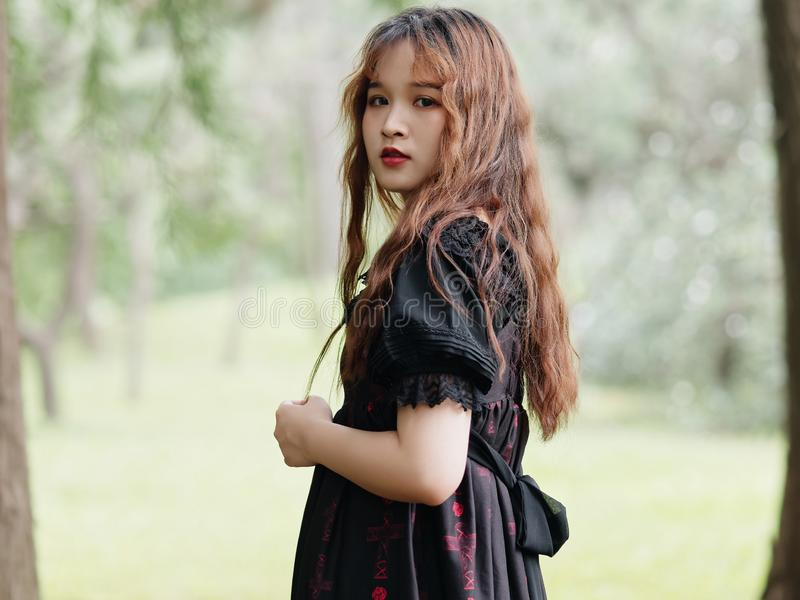 Portrait of beautiful Asian woman standing in summer forest, Chinese girl in vintage black dress looking at camera royalty free stock photography