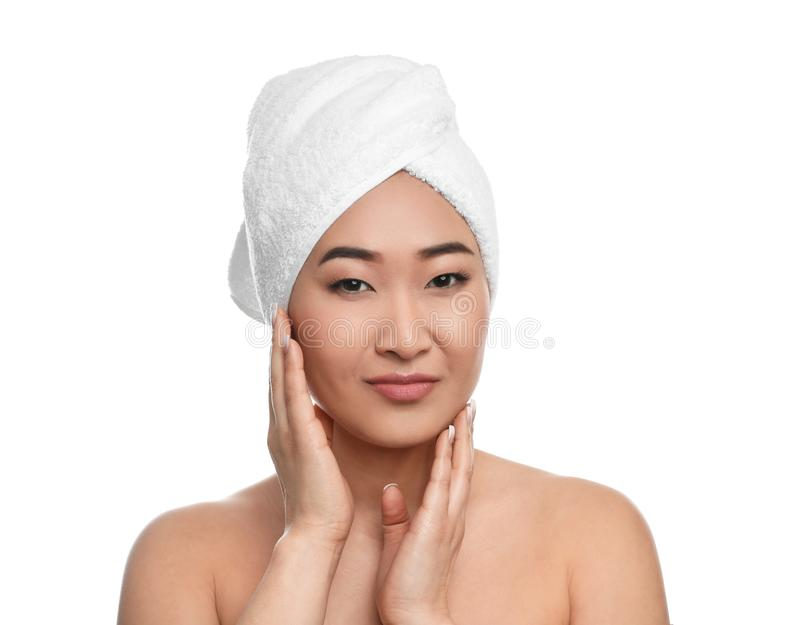 Portrait of beautiful Asian woman with towel on head against white background. Spa treatment stock photography
