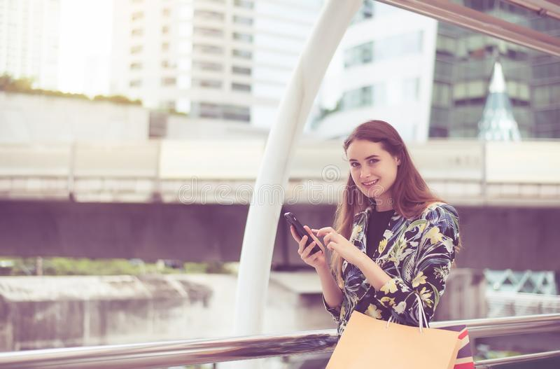 Portrait beautiful asian woman walking and holding mobilephone in the city,Happy and smiling royalty free stock photo