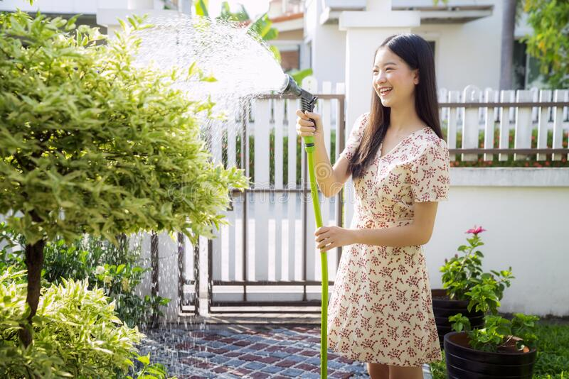 Portrait of beautiful asian woman watering green plants on the balcony royalty free stock photography