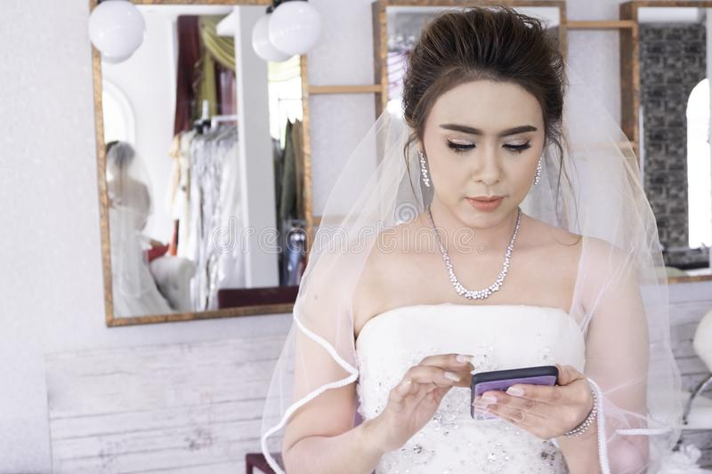 Portrait of beautiful asian women bride in  wedding white dress. Holding using smartphone mobilephone in dressing room. Concept stock images