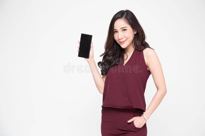 Portrait of beautiful Asian wowan showing or presenting mobile phone. Application on hand isolated over white background stock images