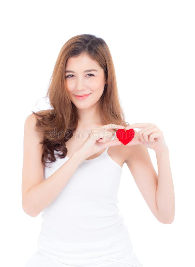 Portrait of beautiful asian young woman holding red heart shape pillow and smile isolated on white background stock photo