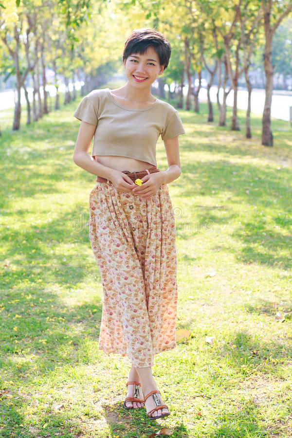 Portrait of beautiful asian young woman with smiling face standi. Ng in flowers blooming park relaxing emotion stock photos