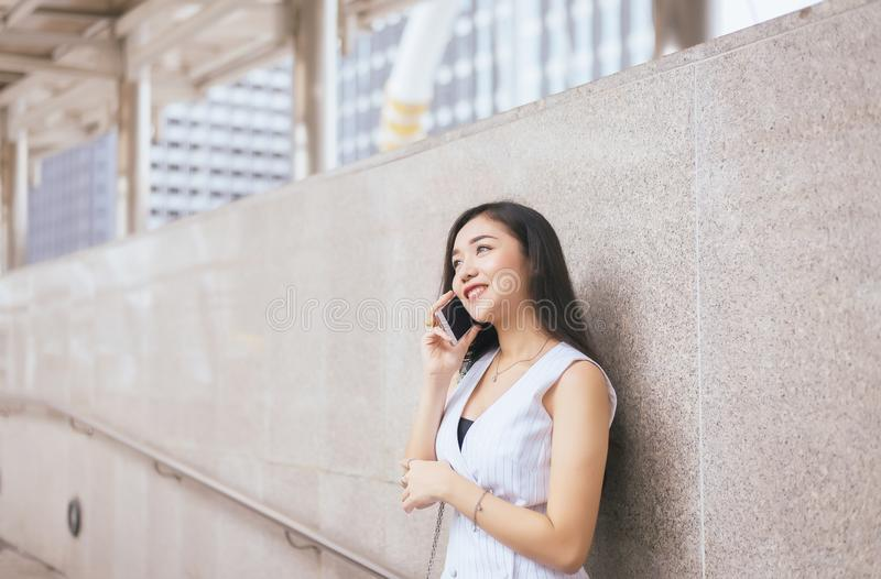 Portrait beautiful asian woman using mobile phone and walking in the center city,Happy and smiling,Female with positive attitude royalty free stock images