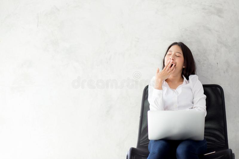 Portrait of beautiful asian young woman yawn at her work place with laptop computer on cement background stock photo