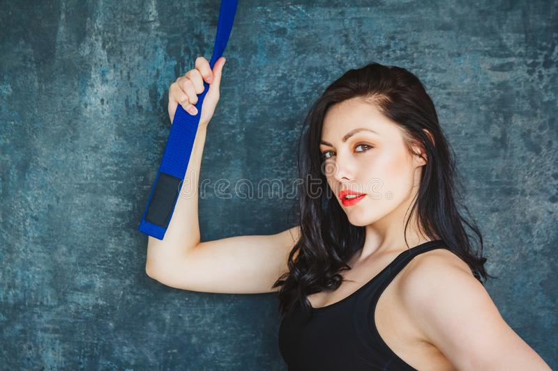 Portrait beautiful athletic woman with blue belt. Martial arts concept. Indoor, studio shot. Set on a gray background stock image