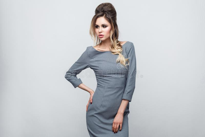 Portrait of beautiful attractive fashion model in grey dress with makeup and hairstyle standing, posing with hand on waist and royalty free stock photography
