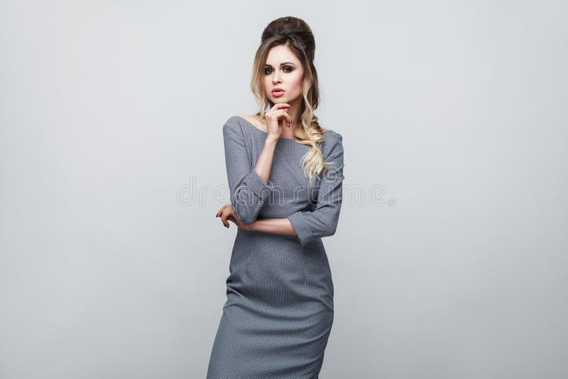 Portrait of beautiful attractive fashion model in grey dress with makeup and hairstyle standing, posing and touching her chin and stock images