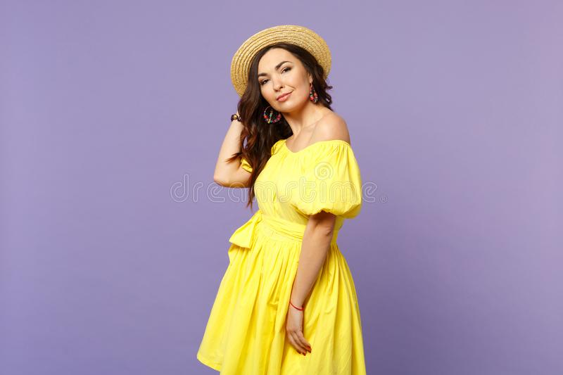 Portrait of beautiful attractive young woman in yellow dress, summer hat looking camera isolated on pastel violet stock photos