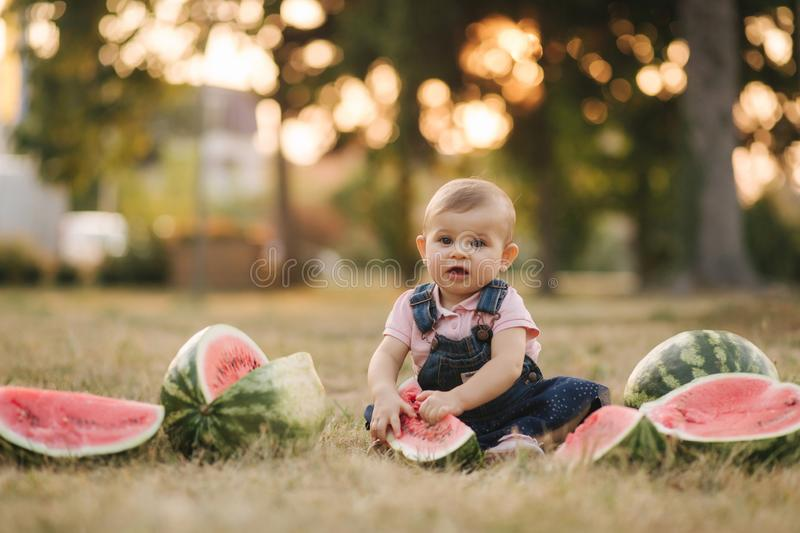 Portrait of beautiful baby girl eating watermelon. Child eating watermelon in the garden. Adorable little girl playing stock photo