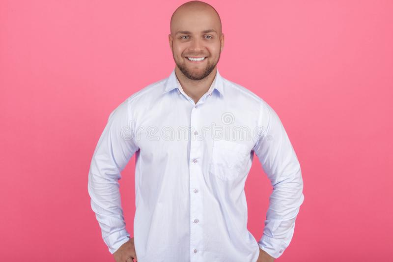 Portrait of a beautiful bald bearded man. he stands and smiles at the camera and holds his arms sideways. isolated on pink wall. royalty free stock photo