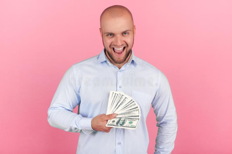 Portrait of a beautiful bald man with a beard dressed in a white shirt. won the lottery happily screming and keeps a packet of mon stock photography