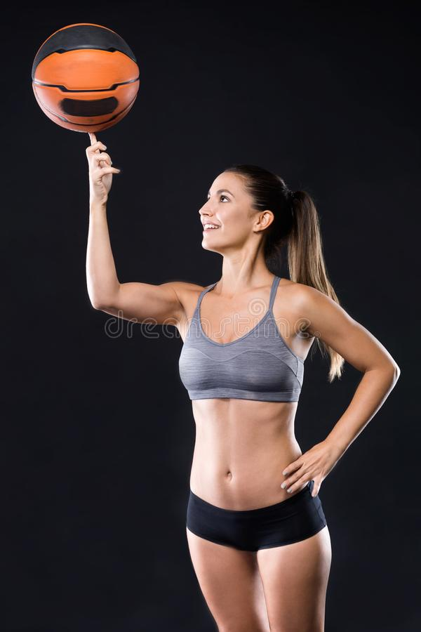 Beautiful basketball player spinning the ball on her finger over black background. royalty free stock photos