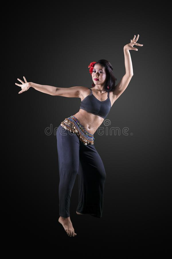 Beautiful belly dancer performing in the studio. Portrait of beautiful belly dancer performing in the studio with black background royalty free stock images