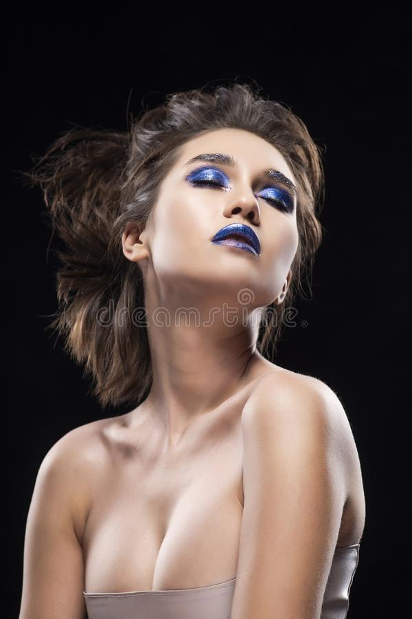 Portrait of a beautiful big breast asian naked shoulders, vanguard conceptual hairstyle and aggressive blue lips makeup girl stock photo