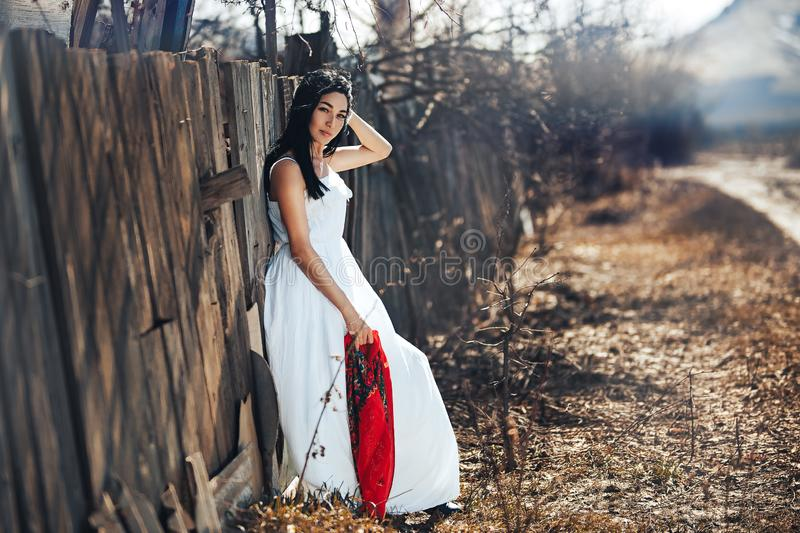 Portrait of a Beautiful black haired girl in a white vintage dress standing near wood fence.Young woman model posing in a russian. National style . red shawl royalty free stock images