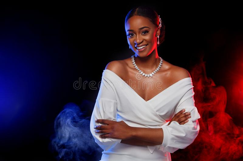 Portrait of beautiful black skin woman. Charming young bride in wedding dress and jewelry on dark background with color. Charming young bride in wedding dress stock image