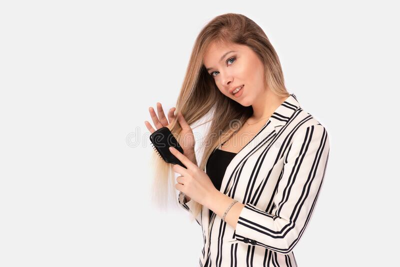 Portrait of Beautiful Blond Business Woman Brushing Her Hair royalty free stock photo