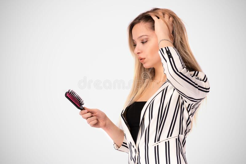 Portrait of Beautiful Blond Business Woman Brushing Her Hair stock images