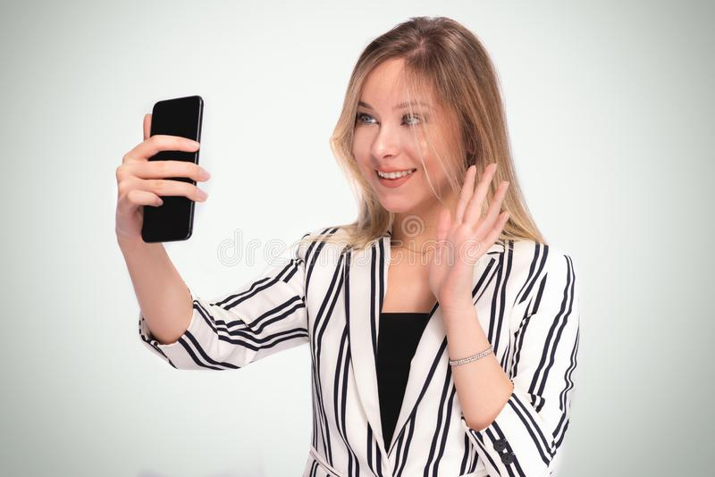 Portrait of Beautiful Blond Business Woman Having Video Chat on Smartphone stock image