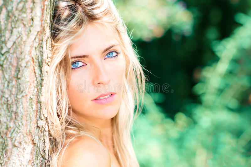 Portrait of beautiful blond girl with blue eyes in nature royalty free stock image