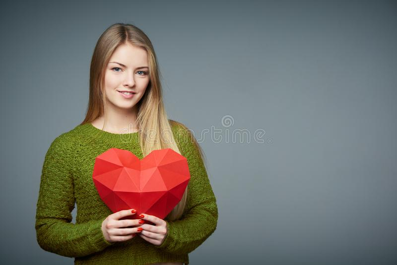 Portrait of beautiful blond girl holding heart shape stock images