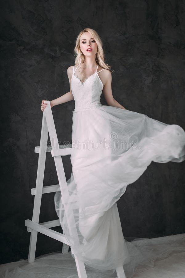 Portrait of a beautiful blond girl in image of the bride . Beauty face. Photo shot in the Studio on a grey background stock image