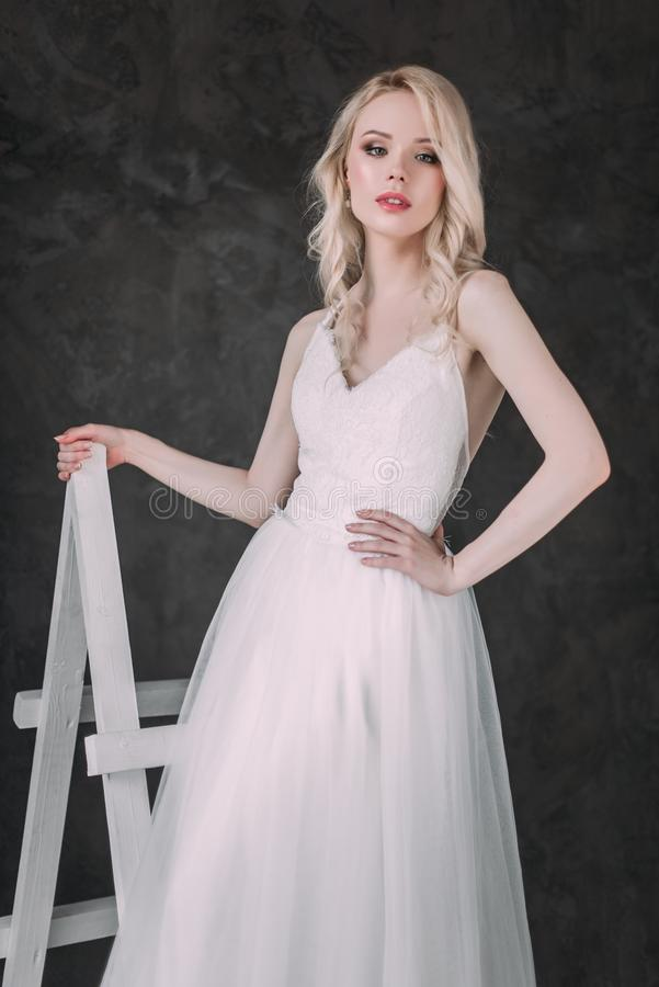 Portrait of a beautiful blond girl in image of the bride . Beauty face. Photo shot in the Studio on a grey background royalty free stock images