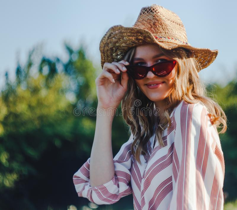 Portrait of the beautiful blond girl with vintage glasses in the park. Young blond woman in the park with vintage glasses royalty free stock image