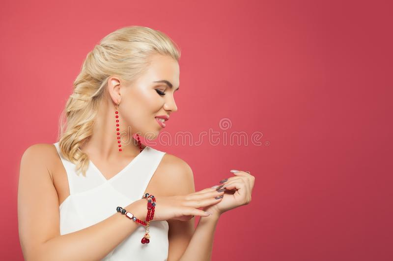 Portrait of beautiful blond hair woman looking at hand with manicured nails on colorful pink background stock photo