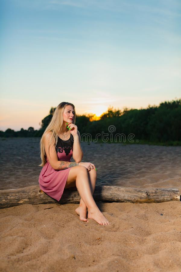 Portrait of the beautiful blond model with long hair on the sand beach. At the background of summer sunset stock photo