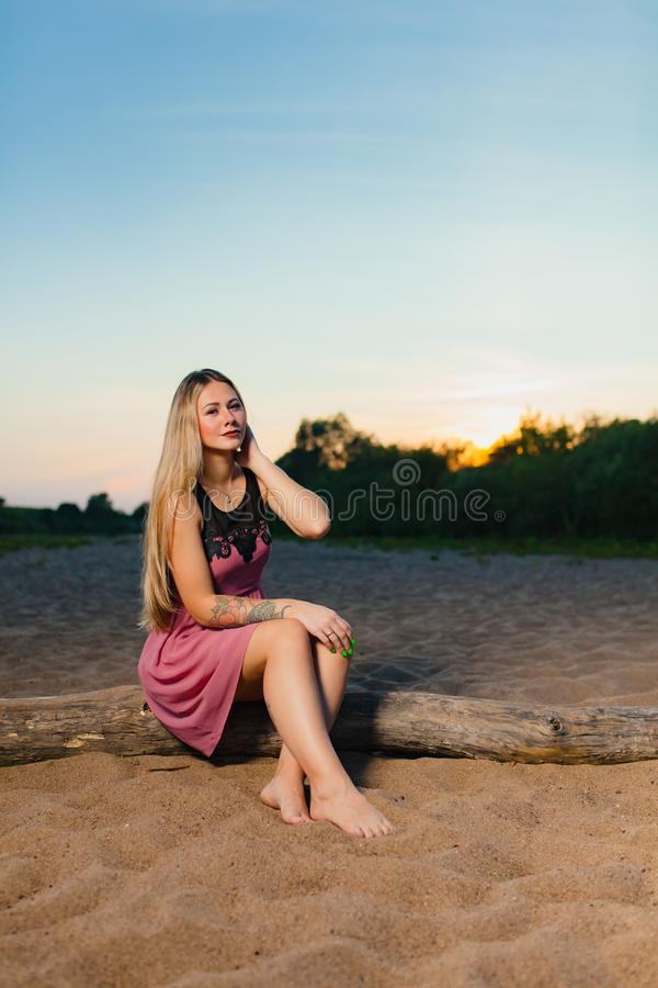 Portrait of the beautiful blond model with long hair on the sand beach. At the background of summer sunset royalty free stock photos