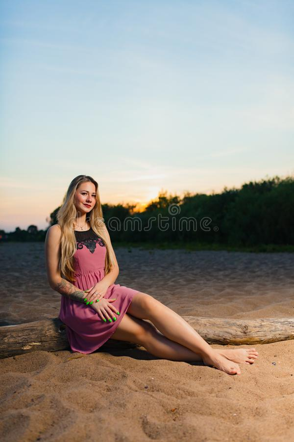 Portrait of the beautiful blond model with long hair on the sand beach. At the background of summer sunset stock photos