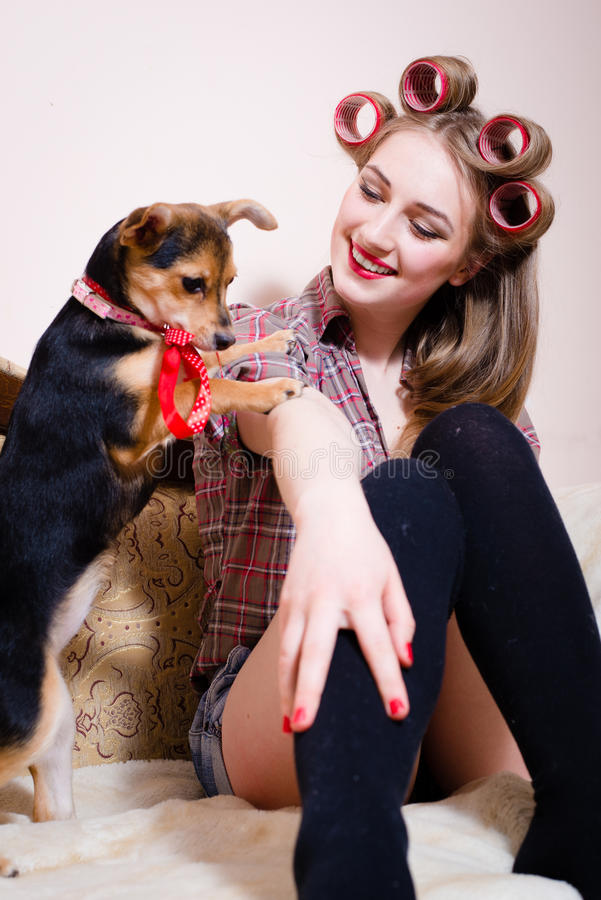 Portrait of beautiful blond pinup girl having fun playing with cute small dog relaxing in bed and happy smiling closeup royalty free stock photo