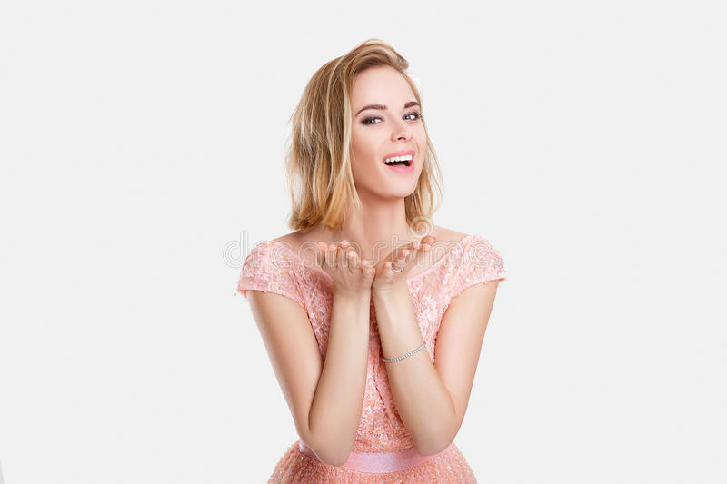 Portrait of beautiful blond woman in pink cocktail dress doing kiss on grey background royalty free stock images