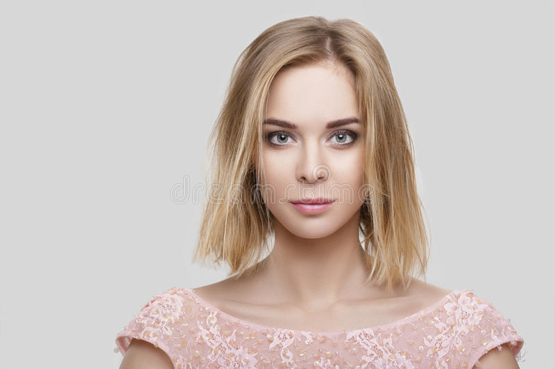 Portrait of beautiful blond woman with short hair in pink cocktail dress on grey background stock photography