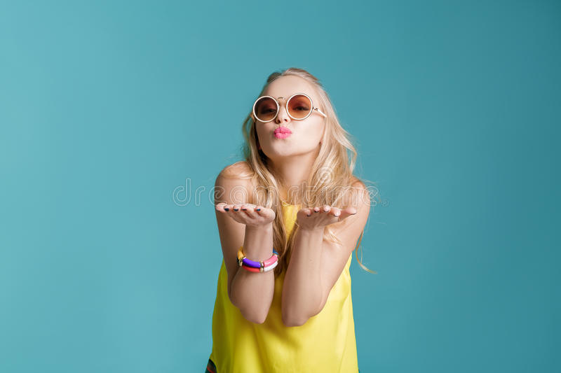 Portrait of beautiful blond woman in sunglasses and yellow shirt on blue background. girl sending air kiss royalty free stock photos